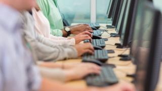 People typing at keyboards