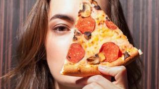 فتاة تمسك بشريحة بيتزا