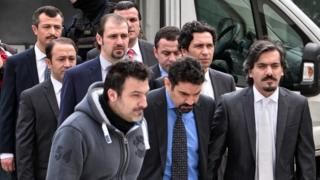 The eight Turkish army officers are escorted by Greek police as they arrive at the Greek Supreme Court on 26 January 2017