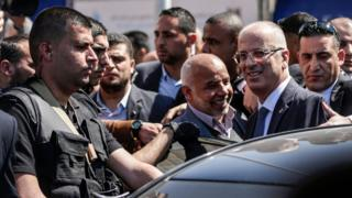 Palestinian Prime Minister Rami Hamdallah (2nd R) is greeted by Hamas security chief Tawfiq Abu Naim (C) upon his arrival in Gaza City on 13 March 2018