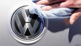 Worker polishes VW logo