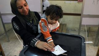 Egyptian woman and her child cast a ballot in the presidential election in Cairo on 26 March 2018