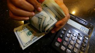 Petugas menghitung uang pecahan dolar Amerika Serikat