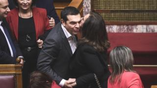 Alexis Tsipras (L) celebrates as he is congratulated following a voting session on the Prespa Agreement on 25 Jan