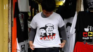 Hanoi vendor wearing T-shirt with Trump and Kim and the word peace on it