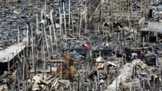 resident gathers charred debris in a slum in Dhaka on 18 August 2019, after a fire broke out late on August 17 at Mirpur neighbourhood