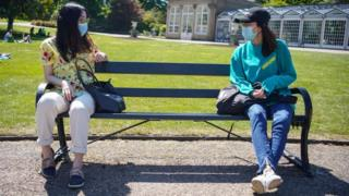 Two people observe social distancing on a bench
