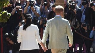 Harry and Meghan being met by the press