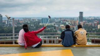 """شباب يلتقطون صورة سيلفي من أعلى بناية """"مركز كينياتا الدولي للمؤتمرات"""" المطل على مدينة نيروبي"""