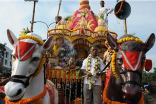 Indian devotees and members of the International Society for Krishna Consciousness (ISKCON) march alongside a chariot carrying a deity during the annual Rath Yatra Festival in Siliguri on June 24, 2009.