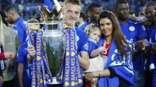 Jamie Vardy lifts the trophy as he celebrates winning the Barclays Premier League as partner Rebekah Nicholson looks on