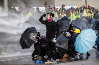 Wanaharakati wa kupigania demokrasia wakijikinga dhidi ya maji ya mwasho kutoka kwa magari polisi wa kizima ghasia Hong Kong mwezi Septemba 15, 2019.