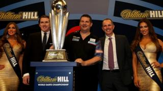 Scotland's Gary Anderson poses with A.P McCoy (second left) after defeating Phil Taylor of England in the final of the 2015 William Hill PDC World Darts Championships at Alexandra Palace 2015 in London