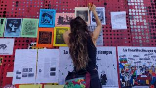 A woman attaches posters