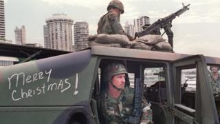 US soldiers man their security position outside the Vatican embassy in Panama City where Panamanian General Manuel Noriega was seeking asylum on 25 December. 1989.