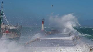 Waves break over the Kalk Bay Harbour wall in Cape Town, South Africa, 14 November 2061. The effect of the supermoon with massive tidal range has combined with a gale force wind and big swell to create this extreme weather phenomenon.