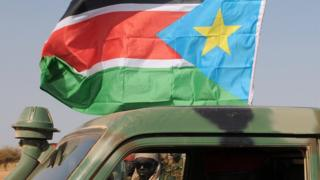 A soldier looking through a military vehicle flying the South Sudanese flag - 2012