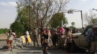 Yemeni pro-government forces backed by a Saudi-led coalition celebrate outside one of the entrances of the key Al-Anad military base in the southern Lahj governorate, some 50km north of the Red Sea port of Aden - 3 August 2015