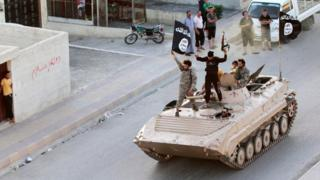 Islamic State militants take part in a military parade along the streets of Raqqa, Syria, on 30 June 2014