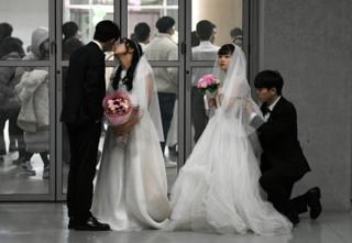 Couples prepare for their performances at a mass wedding ceremony organised by the Unification Church in South Korea.