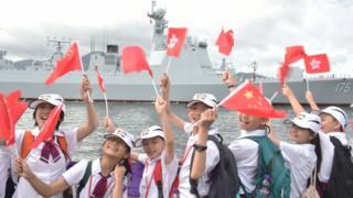 當局安排的學生代表在昂船洲海軍基地迎接遼寧艦編隊(中新社7/7/2017)