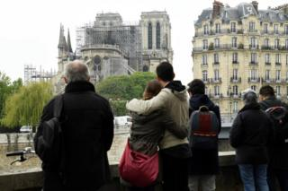 People hug while looking at Notre-Dame
