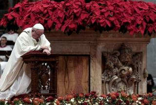 Pope Francis kneels down to pray during a Christmas Eve mass to mark the birth of Jesus Christ at St Peter's Basilica in the Vatican