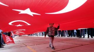 Türk bayrağı altında bir çocuk