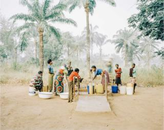 Women and children collect drinking water from a well in Osukputu, Benue, Nigeria