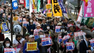 Protesters hold placards outside the National Diet Building during a protest against Japanese Prime Minister Shinzo Abe's cabinet in Tokyo, Japan, 13 March 2018