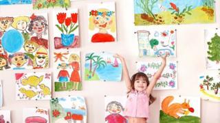 Child showing off artworks
