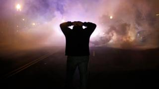 A protester holds his hands up amid tear gas in Ferguson, Missouri