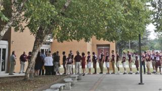 Football players lined up outside Salem High School