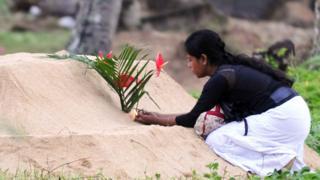Mujer colocando flores en una tumba tras el tsunami de Asia en 2004