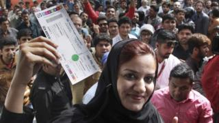 A woman shows a ticket for the upcoming final cricket match of Pakistan Super League while others gather outside a bank to buy tickets in Lahore (01 March 2017)