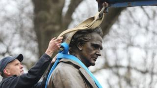 A worker secures the statue of J. Marion Sims before it is driven away, 17 April 2018