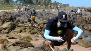Com máscara e roupa com proteção UV, o voluntário Lucas Nelli agachado sobre pedras observando objeto com óleo; no plano de fundo, outros voluntários trabalham na praia