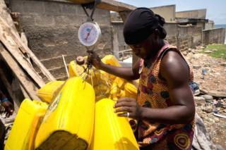 A an weighing jerrycans in La - Accra, Ghana