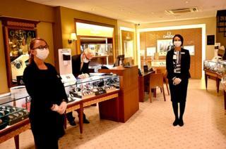 Shop assistants wear masks in a jewellery store
