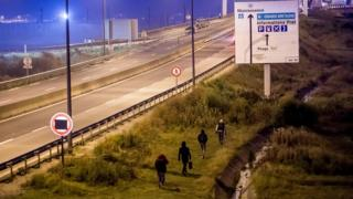 Migrants walk towards Eurotunnel terminal in Coquelles