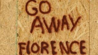 """A sign on a boarded-up building reads """"Go away Florence"""""""