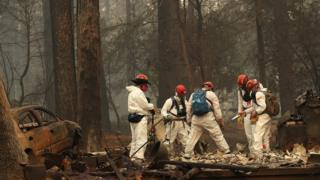 Rescue workers search for human remains at a home that was burned by the Camp Fire