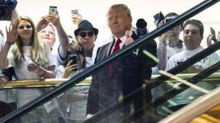 Donald Trump makes his entrance via a golden escalator