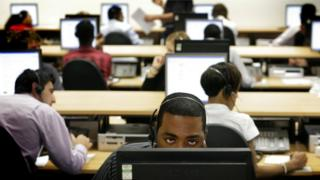 Call centre workers sitting at desks with computers and handsets