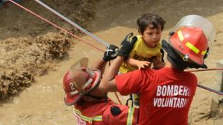 Voluntarios y bomberos rescatando a un niño en Perú.