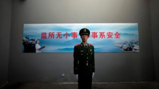 A Chinese paramilitary policeman stands guard underneath a surveillance camera at an entrance to the Number Two Detention Centre in Beijing