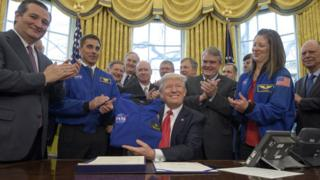 In this handout provided by the National Aeronautics and Space Administration (NASA), President Donald Trump, centre, holds a NASA flight jacket presented to him