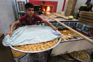 Iraqis prepare pastries known as Kliga ahead of the Eid al-Fitr Muslim festival marking the end of Ramadan, on June 14, 2018 at a pastry shop in Baghdad