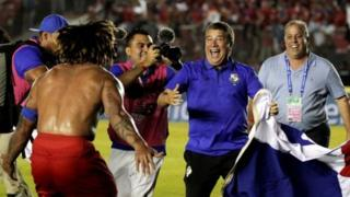 Panama coach Dario Gomez ( wey wear blue) dey celebrate with Roman Torres after dem beat Costa Rica to qualify.