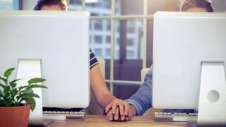 Un hombre y una mujer cuyos rostros no se ven, por estar detrás de unas pantallas de computadora, pero que se toman de la mano